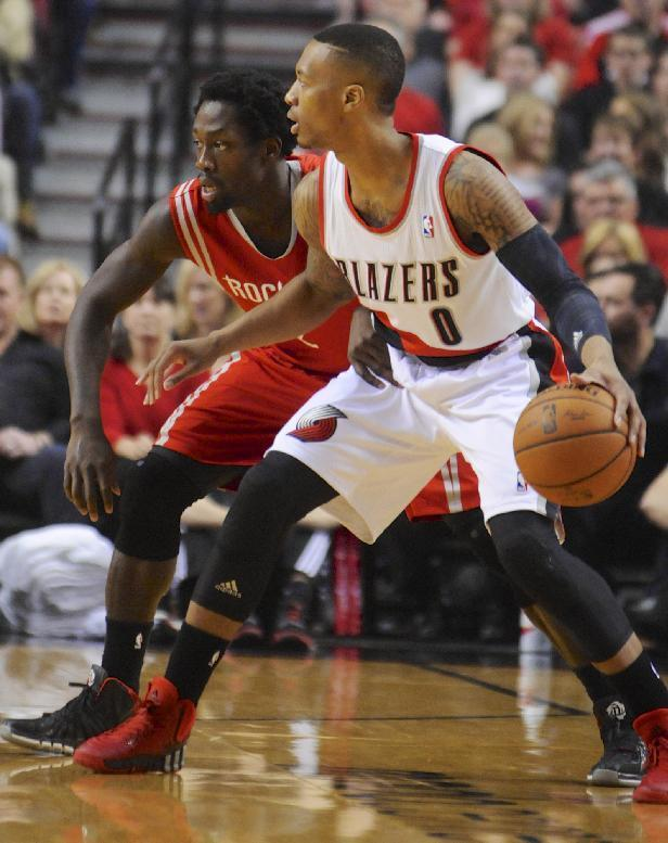Houston Rockets' Patrick Beverley (2) defends against Portland Trail Blazers' Damian Lillard (0) during the first half of game four of an NBA basketball first-round playoff series game in Portland, Ore., Sunday March 30, 2014. (AP Photo/Greg Wahl-Stephens)