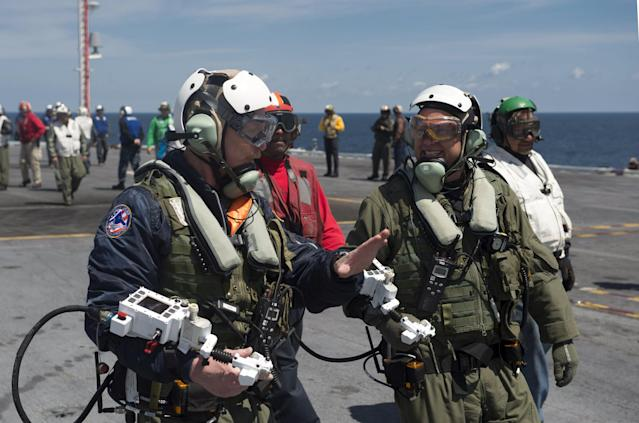 ATLANTIC OCEAN - MAY 14: In this handout released by the U.S. Navy, Dave Lorenz, left, and Bruce McFadden, deck operators for Northrop Grumman, discuss the launch of an X-47B Unmanned Combat Air System (UCAS) demonstrator on the flight deck of the aircraft carrier USS George H.W. Bush (CVN 77) May 14, 2013 in the Atlantic Ocean. Lorenz and McFadden operated the X-47B as it taxied from the aircraft elevator to the catapult. George H.W. Bush is scheduled to be the first aircraft carrier to catapult-launch an unmanned aircraft from its flight deck. The Navy plans to have unmanned aircraft on each of its carriers to be used for surveillance and be armed and used in combat roles. (Photo by Mass Communication Specialist 2nd Class Timothy Walter/U.S. Navy via Getty Images)