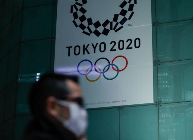 A man wearing a protective face mask following an outbreak of the coronavirus disease (COVID-19) walks past a banner for the upcoming Tokyo 2020 Olympics in Tokyo