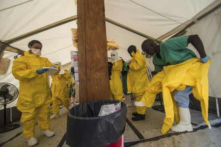 Medical staff working with Medecins sans Frontieres (MSF) put on their protective gear before entering an isolation area at the MSF Ebola treatment centre in Kailahun July 20, 2014. REUTERS/Tommy Trenchard