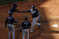 Tampa Bay Rays' Nelson Cruz, right, is congratulated after crossing the plate by Randy Arozarena, top left, Wander Franco (5) and Taylor Walls (6) after clearing the bases on two errors on the play by the Boston Red Sox during the fourth inning of a baseball game Monday, Sept. 6, 2021, at Fenway Park in Boston. (AP Photo/Winslow Townson)