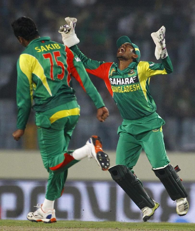 Bangladesh's Shakib Al Hasan, left, joins Anamul Haque as they celebrate the wicket of Pakistan's captain Misbah-ul-Haq during their match in the Asia Cup one-day international cricket tournament in Dhaka, Bangladesh, Tuesday, March 4, 2014. (AP Photo/A.M. Ahad)