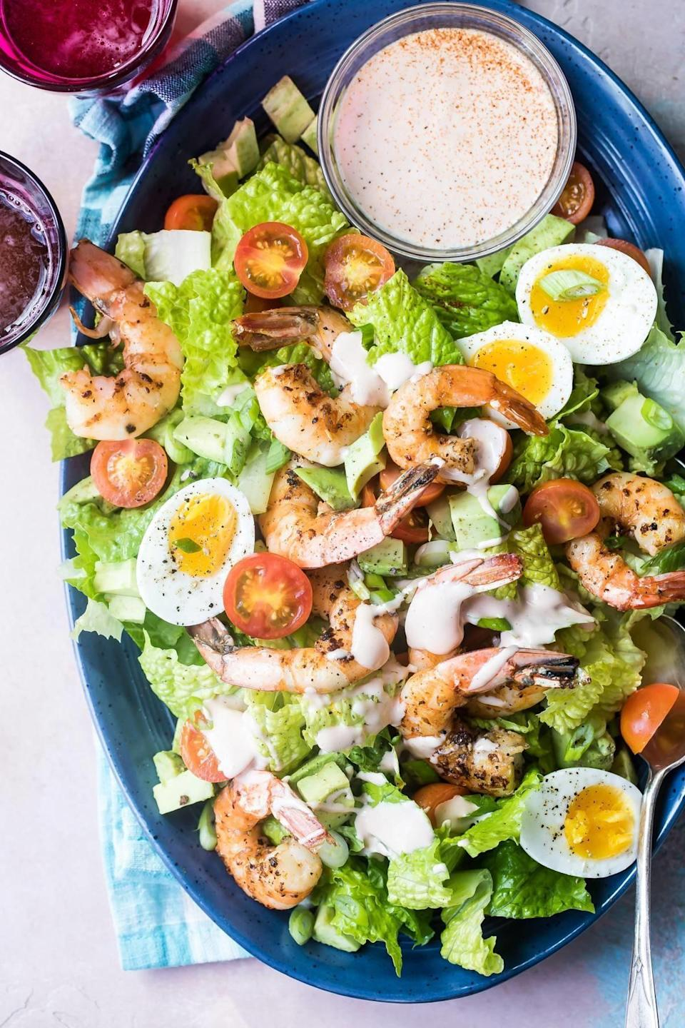Shrimp Louie salad with hard boiled egg, tomato, lettuce, and dressing.