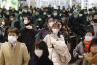 Commuters wear face masks at a station in Fukuoka, southern Japan Thursday, Jan. 14, 2021. Japan expanded a coronavirus state of emergency to seven more prefectures, affecting more than half the population amid a surge in infections across the country. (Naoyuki Shin/Kyodo News via AP)