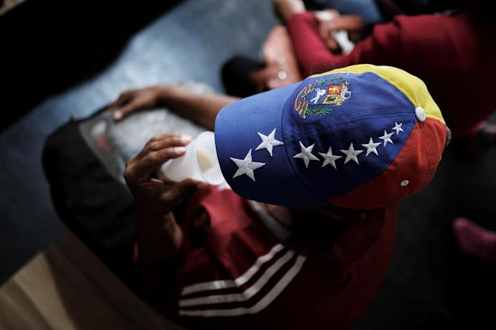 <p>A Venezuelan woman wears a cap with the colors of Venezuelan flag as she drinks coffee with milk after receiving a free vaccination and showing her passport at the Pacaraima border control, Roraima state, Brazil, Aug. 8, 2018. (Photo: Nacho Doce/Reuters) </p>