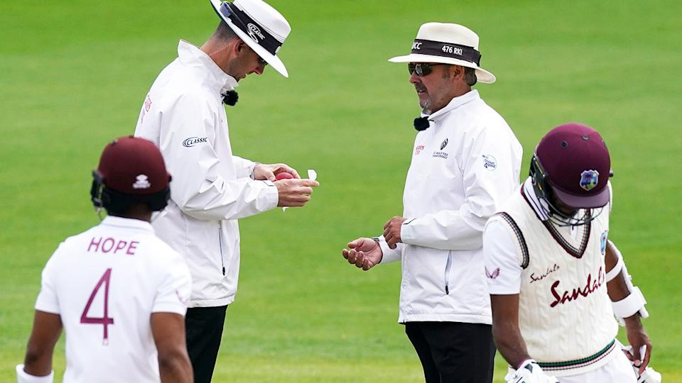 Umpires, pictured here disinfecting the ball during the second Test between England and West Indies.