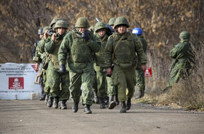 FILE - In this Nov. 9, 2019, file photo, Russia-backed separatist rebels' unit walk to take their position at the new line of contact outside Petrivske, Ukraine. Tensions are rising over the conflict in eastern Ukraine, with growing violations of a cease-fire and a massive Russian military buildup near its border with the region. (AP Photo/Alexei Alexandrov, File)