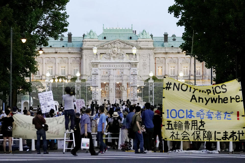"""Protesters against the Tokyo Olympics gather outside Akasaka Palace, Japanese state guest house where the welcome party for IOC President Thomas Bach and its officials are held in Tokyo, Japan, Sunday, July 18, 2021. The banner, yellow, reads """"IOC is a looter ! Use Olympic fees for social welfare"""". (Koji Harada/Kyodo News via AP)"""