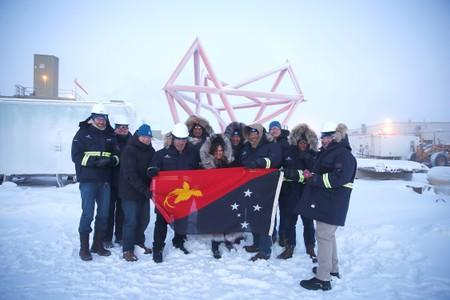 Participants pose for a photo with a Papua New Guinea flag during a stakeholder field trip to Oil Search facilities in Prudhoe Bay