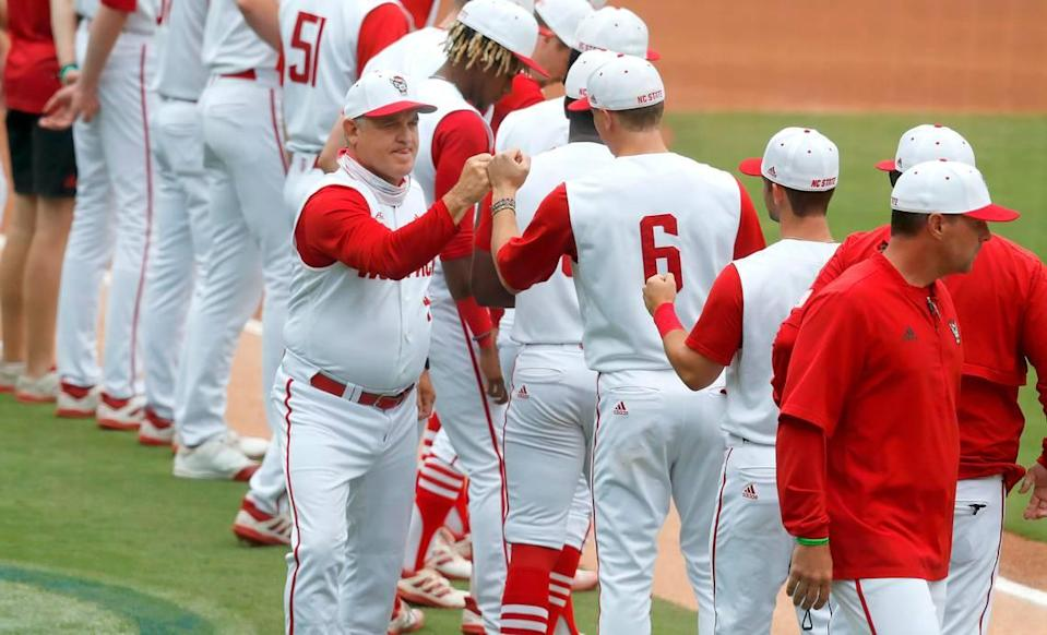 N.C. State head coach Elliott Avent greets players, including Vojtech Mensik (6) during introductions before during N.C. State's game against Duke in the ACC Baseball Championship game at Truist Field in Charlotte, N.C., Sunday, May 30, 2021.