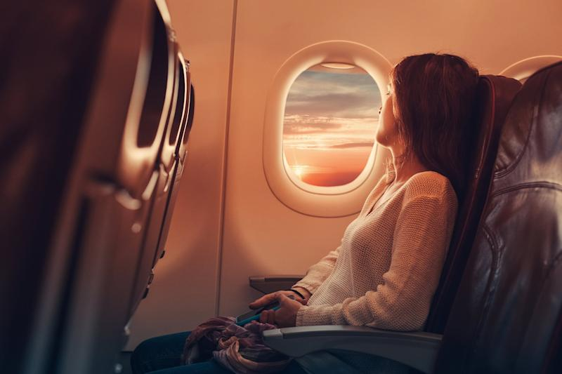 Woman in airplane looking through the window