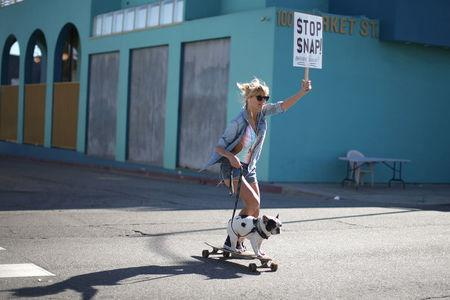 Kristen Schonert skateboards past a Snap Inc. office with a protest sign in Venice, a beach community of Los Angeles, California, U.S., March 2, 2017. REUTERS/Lucy Nicholson