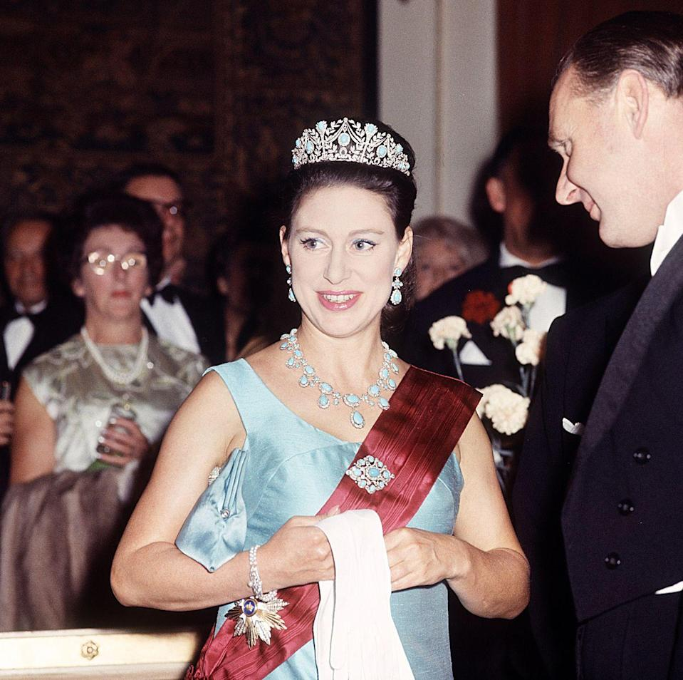 """<p>Princess Margaret wore her cherished Turquoise Parure, this time with the tiara, for a state banquet at the Australian Embassy in 1966. Called <a href=""""https://www.townandcountrymag.com/style/jewelry-and-watches/a20723522/princess-margaret-triumph-of-love-tiara/"""" rel=""""nofollow noopener"""" target=""""_blank"""" data-ylk=""""slk:the Triumph of Love"""" class=""""link rapid-noclick-resp"""">the Triumph of Love</a> for its intricate love knot and laurel wreath design, the tiara was created by the House of Garrard in 1900.</p>"""