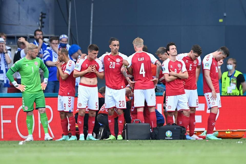 Denmark players protect Christian Eriksen as he receives live-saving treatment during their match against Finland on 12 June