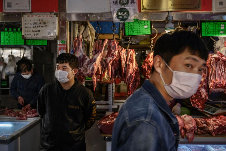 Chinese meat vendors wear protective masks as they wait for customers at a local market in Beijing, China. Source: Getty