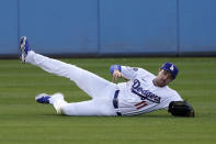 Los Angeles Dodgers left fielder AJ Pollock makes a sliding catch on a ball hit by Washington Nationals' Victor Robles during the first inning of a baseball game Saturday, April 10, 2021, in Los Angeles. (AP Photo/Mark J. Terrill)
