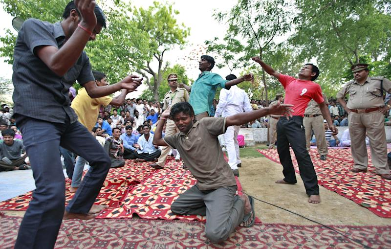 FILE – In this April 26, 2012 file photo, inmates of Tihar jail, the largest complex of prisons in south Asia, dance during a musical evening for inmates in New Delhi, India. India's Tihar Jail is a land of bakeries and carpentry shops, where inmates compete in music contests, take classes and perform intensive Buddhist meditation as part of their rehabilitation. Tihar Jail is also a vast, overcrowded facility, crammed with people awaiting trial who sleep on concrete floors, face daily threats from other prisoners and are shaken down for bribes from their poorly paid jailers, according to human rights lawyers and former inmates there. The two sides of India's most famous jail emerged this week when a man accused in the notorious rape of a woman aboard a New Delhi bus was found dead in his cell, Monday, March 11, 2013, either a suicide, according to jail officials, or a victim of foul play, according to his family. (AP Photo/Saurabh Das, File)
