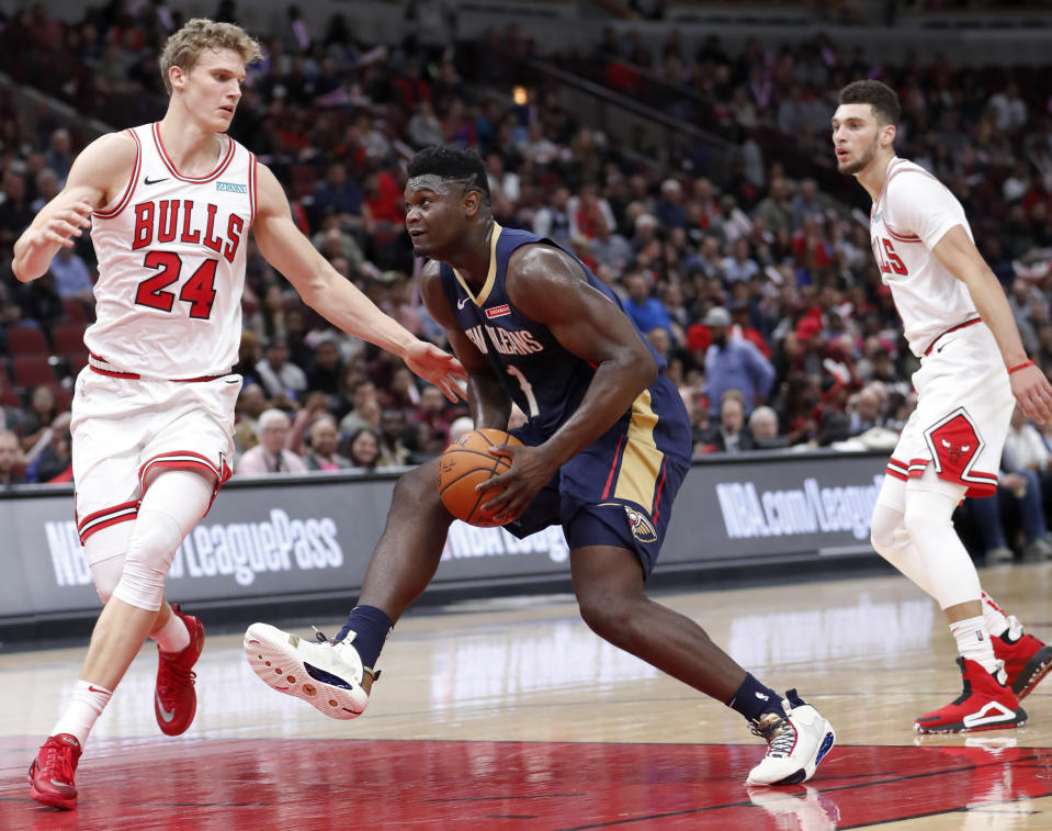 New Orleans Pelicans' Zion Williamson, center, drives to the basket between Chicago Bulls' Lauri Markkanen, left, and Zach LaVine during the first half of an NBA preseason basketball game Wednesday, Oct. 9, 2019, in Chicago. (AP Photo/Charles Rex Arbogast)