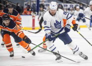 Edmonton Oilers' Evan Bouchard (75) chases Toronto Maple Leafs' William Nylander (88) during first-period NHL hockey game action in Edmonton, Alberta, Monday, March 1, 2021. (Jason Franson/The Canadian Press via AP)