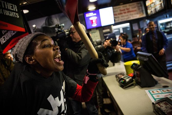 Protesters march through a McDonald's demanding a raise in the minimum wage to $15 per hour on December 4, 2014 in New York (AFP Photo/Andrew Burton)