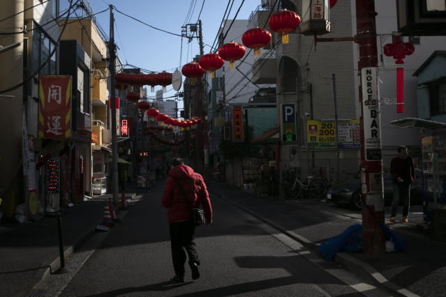 In this Feb. 13, 2020, photo, a man strolls along the empty street adorned with Chinese lanterns in Yokohama's Chinatown, near Tokyo. A top Olympic official made clear Friday the 2020 Games in Tokyo will not be cancelled despite the virus that has spread from China. (AP Photo/Jae C. Hong)