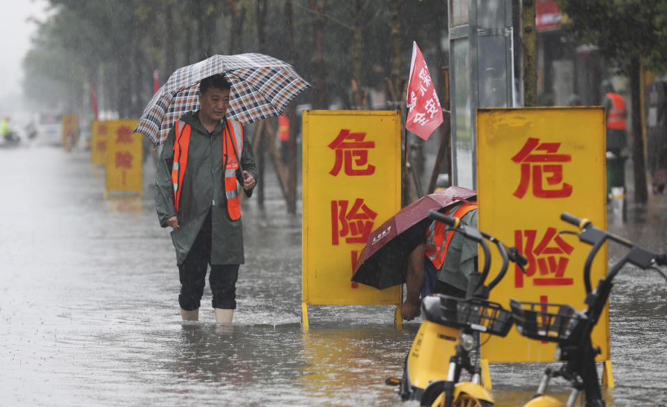 """In this photo released by Xinhua News Agency, staff members set up warning signs with the words """"Danger!"""" at a waterlogged area in Wuzhi County in central China's Henan Province on Tuesday, July 20, 2021. At least a dozen people died in severe flooding Tuesday in a Chinese provincial capital that trapped people in subways and schools, washed away vehicles and stranded people in their workplaces overnight. (Feng Xiaomin/Xinhua via AP)"""