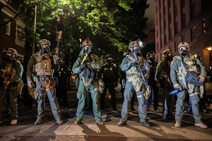 "Federal officers block a downtown street on September 19, 2020 in Portland, Oregon. Protests against police brutality and racial injustice resumed this weekend after activists called for a pause in response to hazardous air quality from nearby wildfire smoke. <span class=""copyright"">Nathan Howard/Getty Images</span>"