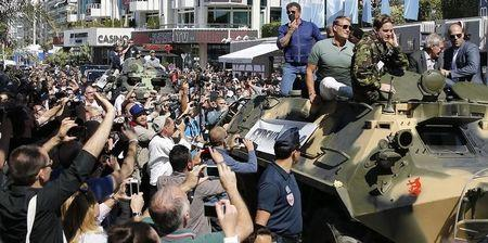 "Cast members Sylvester Stallone (L), Dolph Lundgren (2ndL), Harrison Ford (2ndR) and Jason Statham pose on a tank as they arrive on the Croisette to promote the film ""The Expendables 3"" during the 67th Cannes Film Festival in Cannes May 18, 2014. REUTERS/Regis Duvignau"