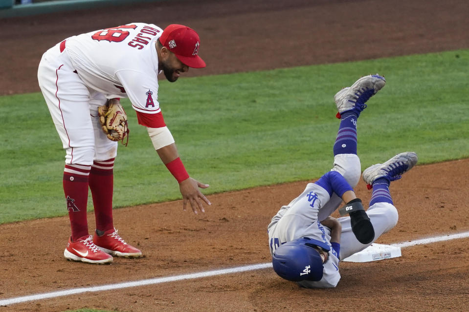 Los Angeles Dodgers' Mookie Betts (50) reacts after Los Angeles Angels third baseman Jose Rojas (18) hit him in the groin area as Rojas caught a ball at third base during the fourth inning of a baseball game Saturday, May 8, 2021, in Anaheim, Calif. Betts stayed in the game. (AP Photo/Ashley Landis)