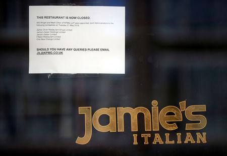 A sign informing the closure of a Jamie's Italian is seen on the door to the restaurant in London