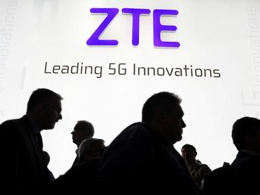Visitors pass in front of the Chinese telecoms equipment group ZTE at MWC 2018. Image: Reuters