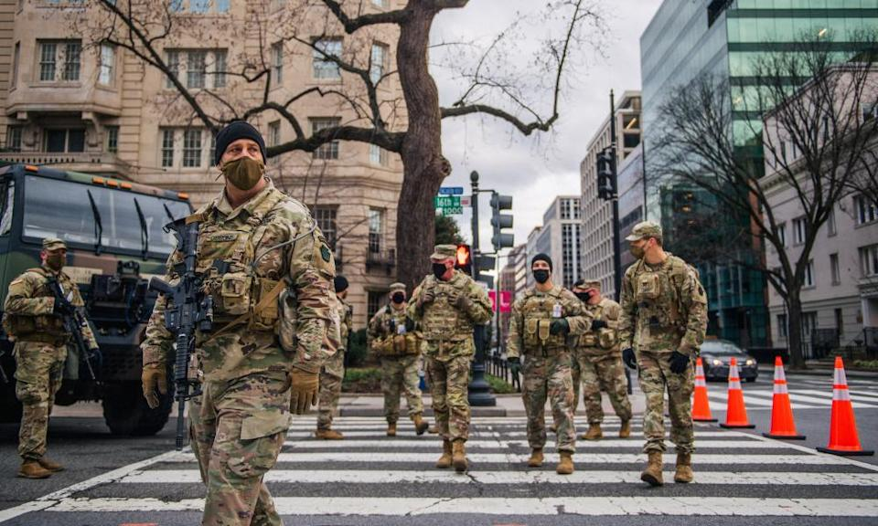 National guard troops walk the streets in Washington DC on 17 January.