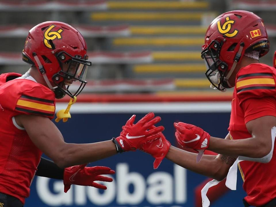 Jalen, left, and Tyson Philpot have a friendly rivalry on the field they say pushes them both to succeed. (David Moll/Calgary Dinos - image credit)