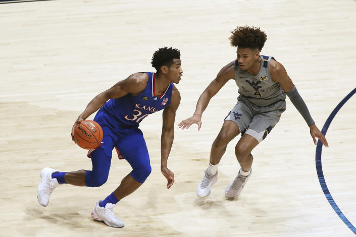 Kansas guard Ochai Agbaji (30) is defended by West Virginia guard Miles McBride (4) during the first half of an NCAA college basketball game Saturday, Feb. 6, 2021, in Morgantown, W.Va. (AP Photo/Kathleen Batten)