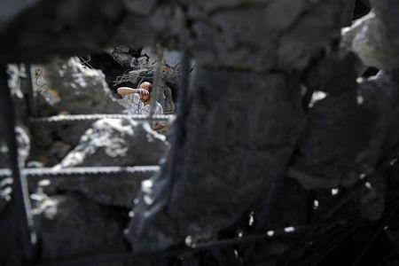 Palestinian man is seen through the rubble of an apartment block that was hit by an Israeli air strike, in the northern Gaza Strip