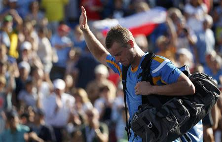 Lleyton Hewitt of Australia waves as he departs after losing his match against Mikhail Youzhny of Russia at the U.S. Open tennis championships in New York September 3, 2013. REUTERS/Adam Hunger