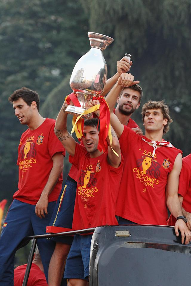 MADRID, SPAIN - JULY 02: Cesc Fabregas of Spain holds the UEFA EURO 2012 trophy aloft as he celebrates with team-mates during a victory parade on an open-top bus on July 2, 2012 in Madrid, Spain. Spain beat Italy 4-0 in the UEFA EURO 2012 final match in Kiev, Ukraine, on July 1, 2012. (Photo by Oli Scarff/Getty Images)