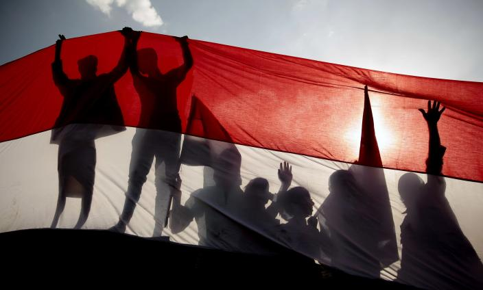 FILE - In this Sept. 26, 2016 file photo, men are silhouetted against a large representation of the Yemeni flag as they attend a ceremony to mark the anniversary of North Yemen's 1962 revolution in Sanaa, Yemen. On Monday, March 22, 2021, Saudi Arabia announced a plan to to offer Yemen's Houthi rebels a cease-fire in the country's yearslong war and allow a major airport to reopen in its capital. The Houthis offered no immediate comment to the proposal. (AP Photo/Hani Mohammed, File)