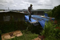 Wilfredo Negron stands on the rooftop of one of his properties securing the zinc roof in preparation for the current hurricane season, in Corozal, Puerto Rico, Monday, July 13, 2020. Nearly three years after Hurricane Maria tore through Puerto Rico, tens of thousands of homes remain badly damaged, many people face a new hurricane season under fading blue tarp roofs and the latest program to solve the housing crisis hasn't yet finished a single home. (AP Photo/Carlos Giusti)