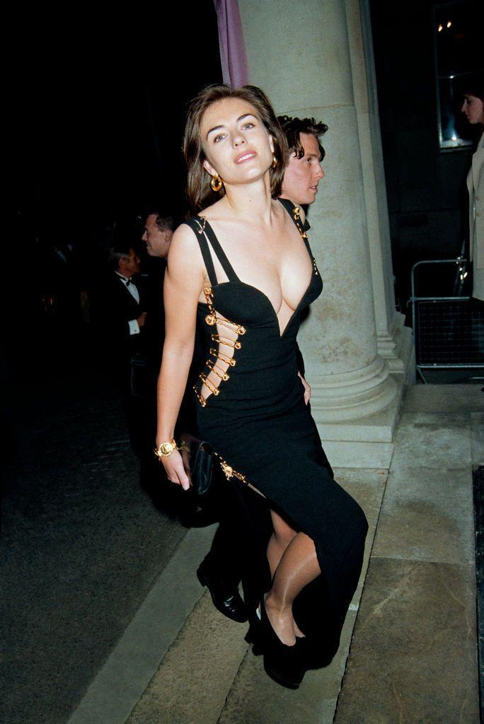 """<p>Before Elizabeth Hurley attended the <em>Four Weddings and a Funeral</em> movie premiere with Hugh Grant in 1994, she was pretty much unknown. But <a href=""""https://www.msn.com/en-us/lifestyle/lifestyle-buzz/the-untold-fashion-story-of-elizabeth-hurleys-iconic-versace-safety-pin-dress/ss-BB17yH9V"""" rel=""""nofollow noopener"""" target=""""_blank"""" data-ylk=""""slk:that all changed"""" class=""""link rapid-noclick-resp"""">that all changed </a>when she showed up in this plunging Versace creation held together with large gold safety pins. The dress <a href=""""https://www.instyle.com/celebrity/iconic-dresses-anniversary-issue"""" rel=""""nofollow noopener"""" target=""""_blank"""" data-ylk=""""slk:catapulted both Versace and Elizabeth Hurley herself"""" class=""""link rapid-noclick-resp"""">catapulted both Versace and Elizabeth Hurley herself</a> to a new level of fame. </p>"""