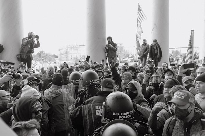 Capitol police walk through a crowd of Trump supporters outside of the Capitol.