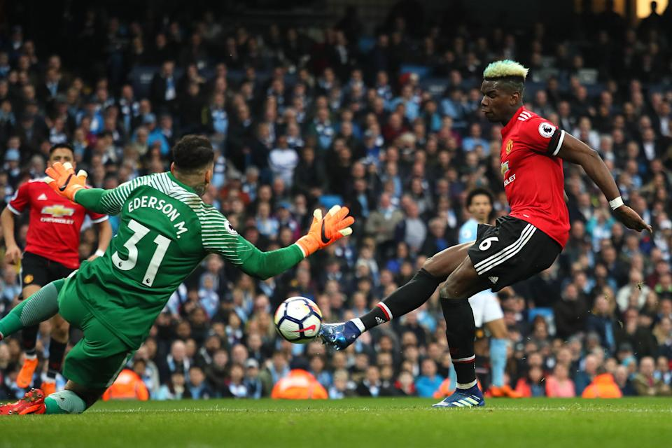Paul Pogba scores one of his two goals past Ederson in the derby between Manchester United and Manchester City. (Getty)