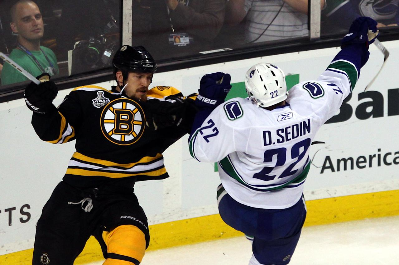 BOSTON, MA - JUNE 06:  Andrew Ference #21 of the Boston Bruins checks Daniel Sedin #22 of the Vancouver Canucks during Game Three of the 2011 NHL Stanley Cup Final at TD Garden on June 6, 2011 in Boston, Massachusetts.  (Photo by Bruce Bennett/Getty Images)