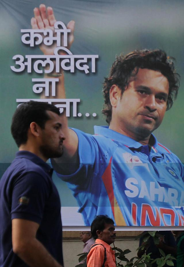 "Indians walk past a giant hoarding with a portrait of Indian cricket player Sachin Tendulkar and a message that reads ""Never say Farewell"" in Mumbai, India, Thursday, Nov. 14, 2013. Tendulkar plays his world-record 200th and last test from Thursday in a hometown stadium before retiring from international cricket.(AP Photo/Rafiq Maqbool)"