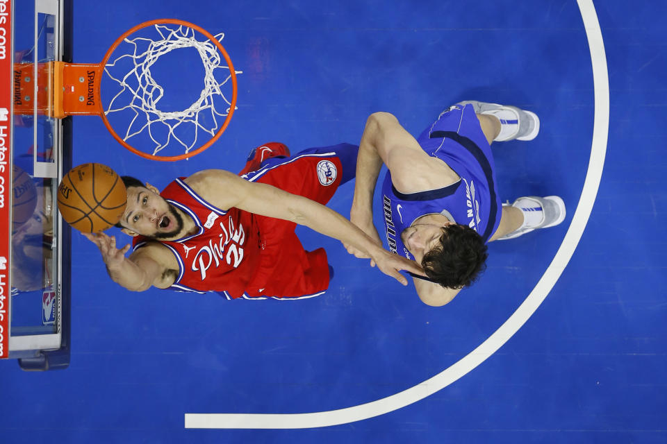 Philadelphia 76ers' Ben Simmons, left, goes up for a shot against Dallas Mavericks' Boban Marjanovic during the first half of an NBA basketball game, Thursday, Feb. 25, 2021, in Philadelphia. (AP Photo/Matt Slocum)