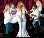 <p>Carey also provided us with one of our favorite onstage wardrobe changes ever, assembling a team to switch out her bling sling with another covered with fur. <i>(Photo: Getty)</i></p>