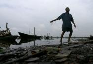 A man throws dead fish back into a polluted river in Ogoniland, Rivers State