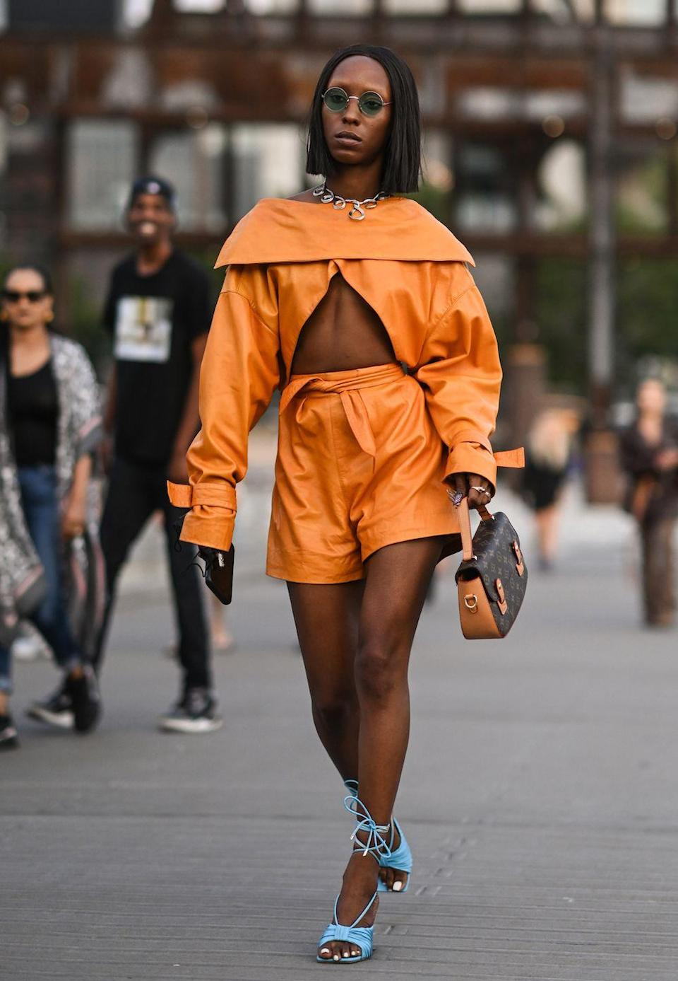 <p>Dalia Drake is seen wearing an orange top and shorts and baby blue heels with a Louis Vuitton bag outside the Proenza Schouler show.</p>