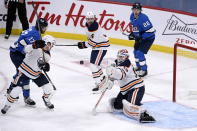 Edmonton Oilers goaltender Mikko Koskinen (19) makes a save against the Winnipeg Jets during the second period of an NHL hockey game, Sunday, Jan. 24, 2021 in Winnipeg, Manitoba. (Fred Greenslade/The Canadian Press via AP)