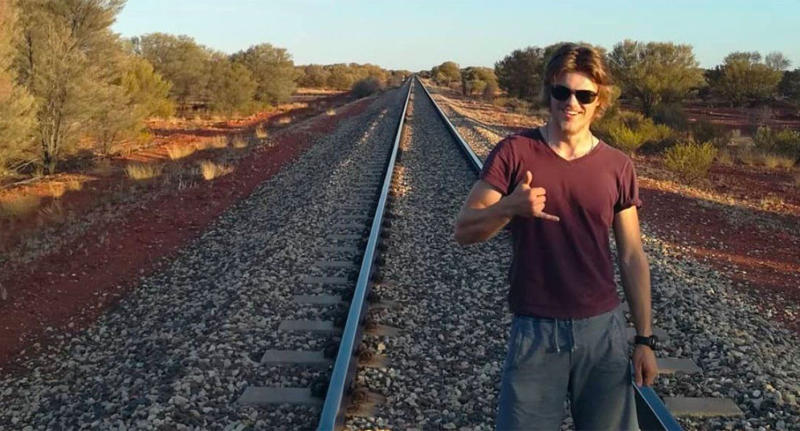 Backpacker Theo Hayez poses for a photo on train tracks.